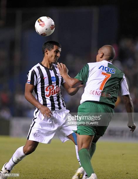 Alianza Lima's Edgar Gonzalez vies for the ball with Libertad's Sergio Aquino during their Copa Libertadores football match in Asuncion on February 9...
