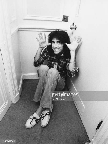 Alice Cooper US rock singer sitting on the floor while looking up at the camera and gesturing with his hands at the Savoy Hotel in London England...