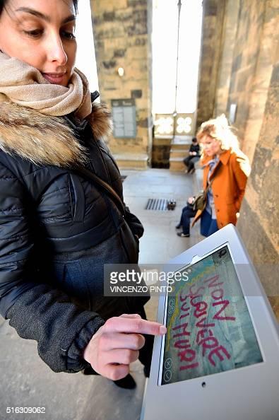 Alice Filipponi from the Opera di Santa Maria del Fiore writes a digital graffiti reading 'Do not write on walls' on a tablet screen on March 17 2016...