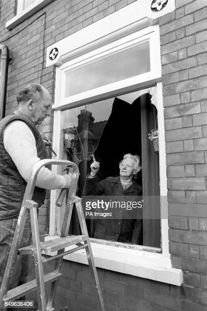 Alice Howarth and a glazier inspect one of her windows which was damaged when violence broke out in Ivy Road as fans left the Luton Town and Millwall...
