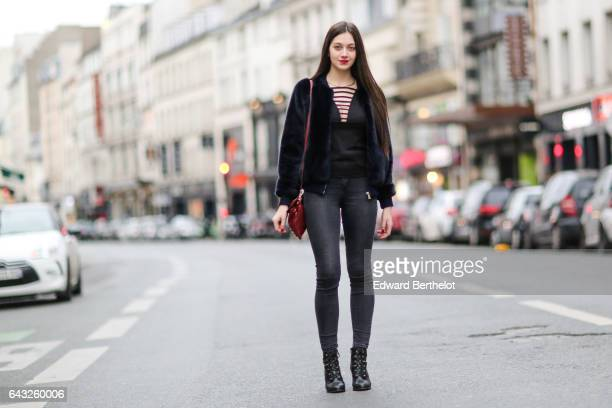 Alice Mouzon wears HM gray denim jeans pants HM black shoes a Trussardi dark blue faux fur coat a black low neck top and a Balenciaga red bag on...