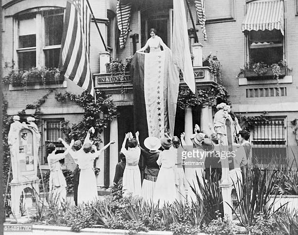 Alice Paul unfurls a banner from the balcony of the National Women's Party headquarters showing a star for each state which has ratified the 19th...