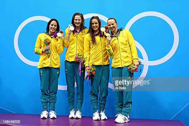 Alicia Coutts Cate Campbell Brittany Elmslie and Melanie Schlangerof Australia celebrate with their gold medalis and their counrty's flag during the...