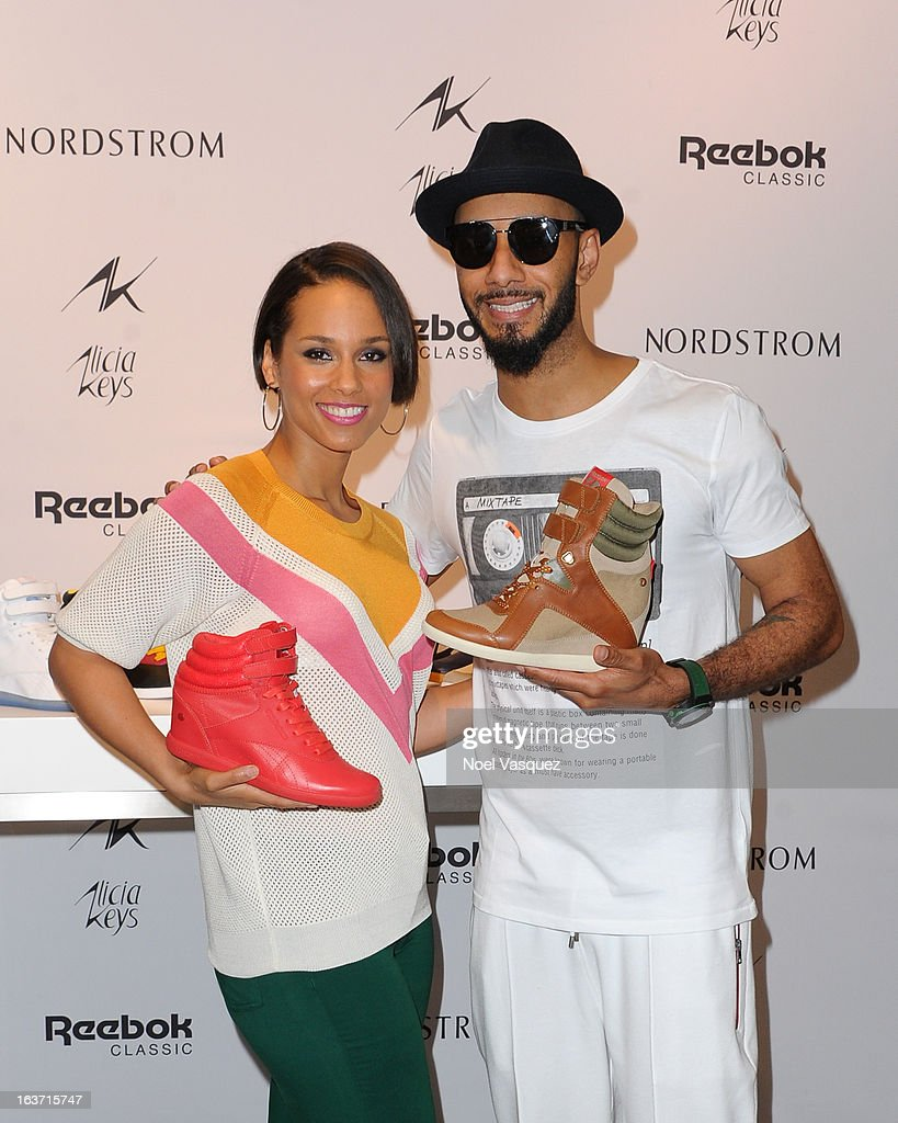 Alicia Keys (L) and husband Swizz Beatz display her new 'AKW' shoe from Reebok at 'Extra' at The Grove on March 14, 2013 in Los Angeles, California.