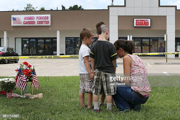 Alicia Nerren prays with her children as they pay their respects to those killed while visiting a memorial placed in front of the Armed Forces Career...