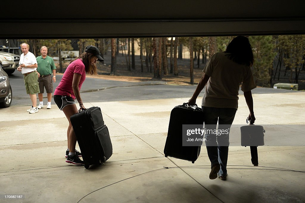 Alicia Taylor and her mother Lana Forey hurry from their house with their bags as some residents were allowed back into the Black Forest Fire area to quickly get medications and important items that were left behind in the rush to evacuate near Colorado Springs, Colorado. June 14, 2013 Denver, Colorado Springs.