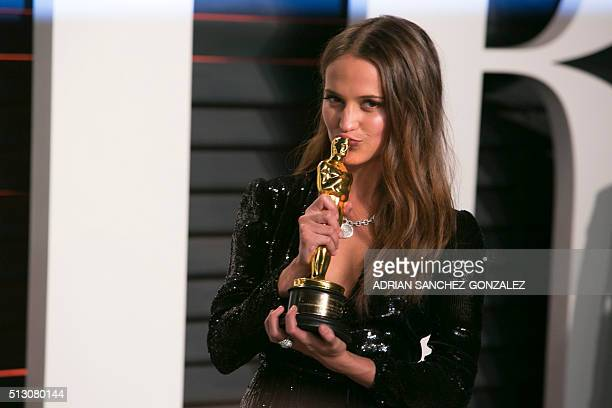 Alicia Vikander holds her Oscar for best supporting actress in her role 'The Danish Girl' as she arrives to the 2016 Vanity Fair Oscar Party February...