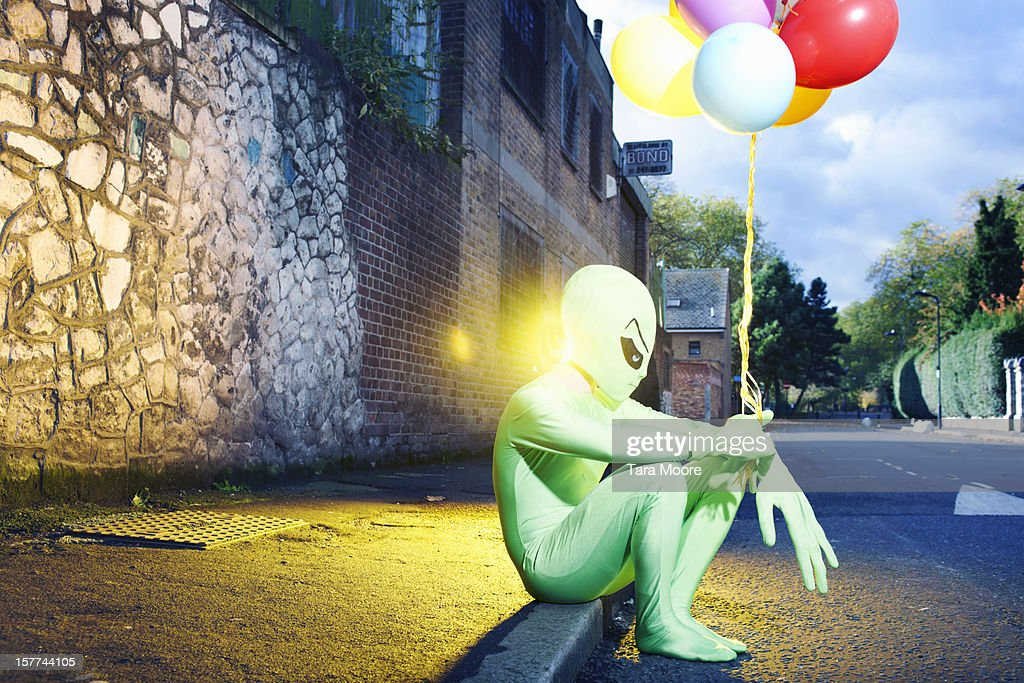 alien sitting in street with balloons