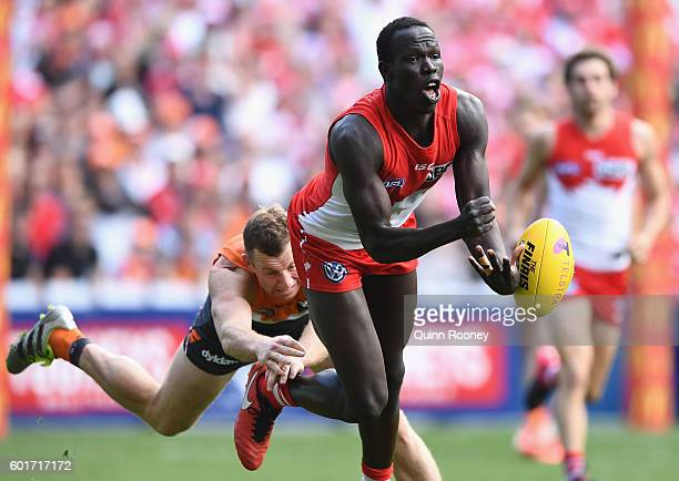 Aliir Aliir of the Swans handballs whilst being tackled by Steve Johnson of the Giants during the AFL 1st Qualifying Final match between the Sydney...