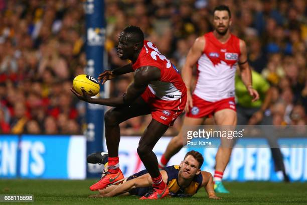 Aliir Aliir of the Swans slips a tackle by Jack Redden of the Eagles during the round four AFL match between the West Coast Eagles and the Sydney...