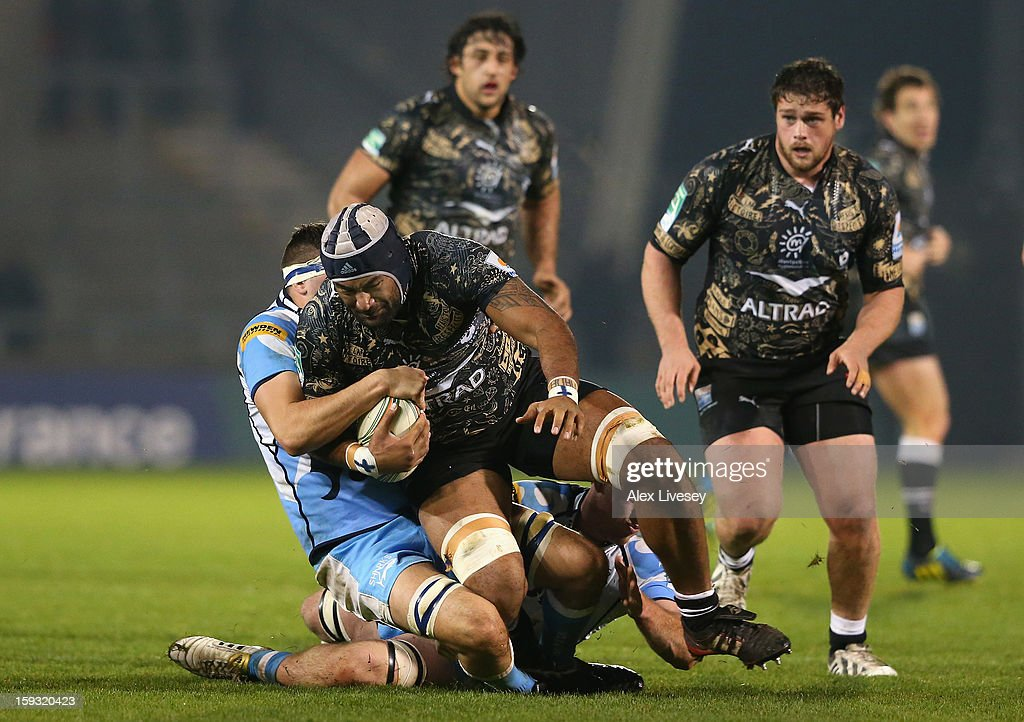 Aliki Fakate of Montpellier is tackled by Tom Holmes of Sale Sharks during the Heineken Cup Pool 6 match between Sale Sharks and Montpellier at Salford City Stadium on January 11, 2013 in Salford, England.