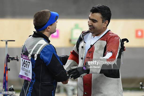 Alin George Moldoveanu of Romania celebrates winning the gold medal with bronze medal winner Gagan Narang of India in the Men's 10m Air Rifle...