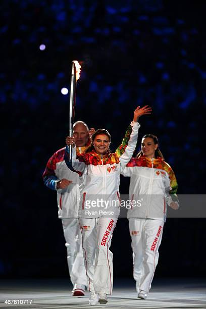 Alina Kabaeva carries the Olympic torch into the stadium during the Opening Ceremony of the Sochi 2014 Winter Olympics at Fisht Olympic Stadium on...