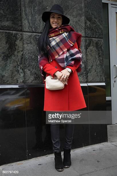 Alina Nunu is seen on Michigan Avenue wearing a red wool Zara coat plaid Zara throw black Zara hat and black wax Zara pants on December 12 2015 in...