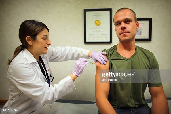 Alina Pastoriza Garcia ARNPNPC administers a flu vaccination to Russell Waddey at the CVS/pharmacy's MinuteClinic on December 4 2012 in Miami Florida...
