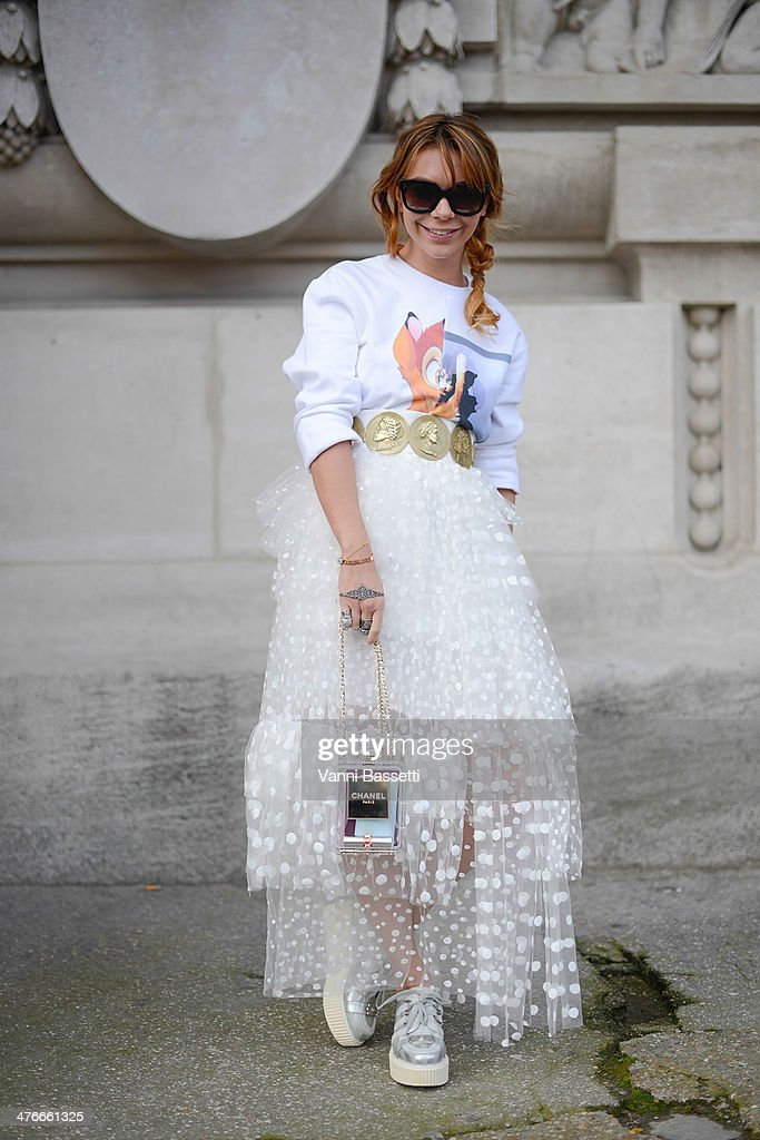Aline Kaltsidou poses wearing a Givenchy sweater, Dolce & Gabbana belt, Chloe skirt, Chanel bag and shoes and Celine sunglasses after the Chanel show at the Grand Palais on March 4, 2014 in Paris, France.