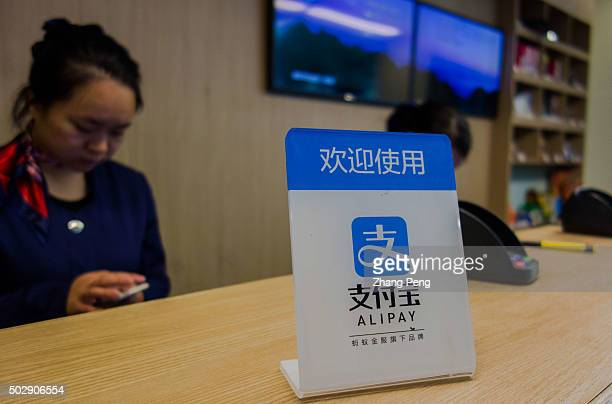 Alipay's signboard is placed on a hotel's counter More and more shops welcome people to pay with Alipay Alibabas Alipay mobile payments service has a...