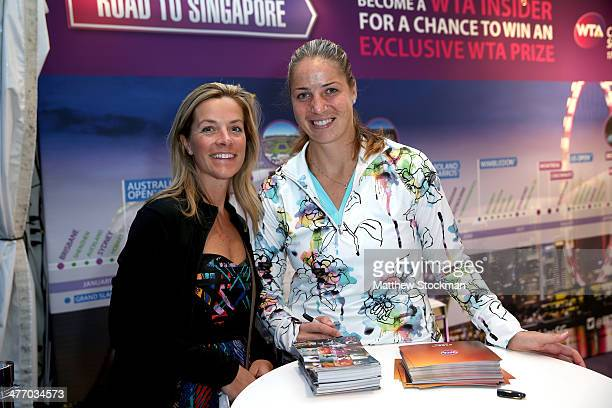 Alisa Kleybanova of Russia signs autographs and poses for pictures at the WTA booth during the BNP Parabas Open at the Indian Wells Tennis Garden on...
