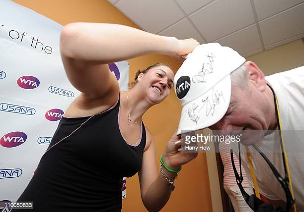 Alisa Kleybanova of Russia signs autographs on a hat for a fan during the BNP Paribas Open at the Indian Wells Tennis Garden on March 13 2011 in...