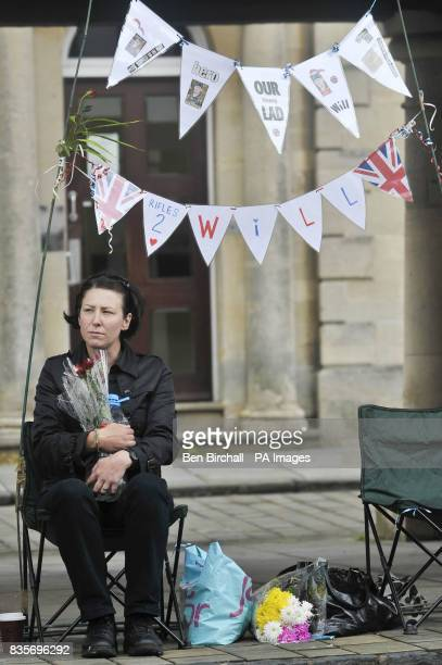Alison Aldridge from Bristol sits and waits for the repatriation procession through Wootton Bassett with her banners dedicated to her nephew Will...