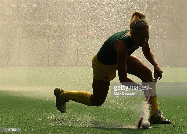 Alison Bruce of the Australian Womens Hockey team trains under the sprinkler system at the Major Dhyan Chand National Stadium ahead of the Delhi 2010...