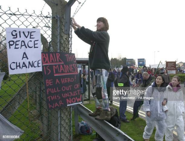 Alison Jones from Winscombe Somerset puts a sign on the perimeter fence as part of the demostration outside the US air base at RAF Fairford...