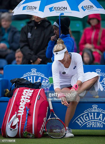 Alison Riske of USA cleans the soles of her shoes during suspended play on day seven of the WTA Aegon Open Nottingham at Nottingham Tennis Centre on...