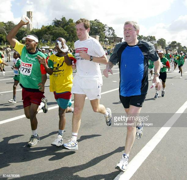 Alistair Campbell and Brendan Foster cross the finish line together after taking part in the Great Ethiopian Run 2003 in Addis Ababa Ethiopia