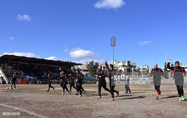 AlIttihad players gesture to their fans as they warmup ahead of the Syrian league football match between derby rivals AlIttihad and AlHurriya on...