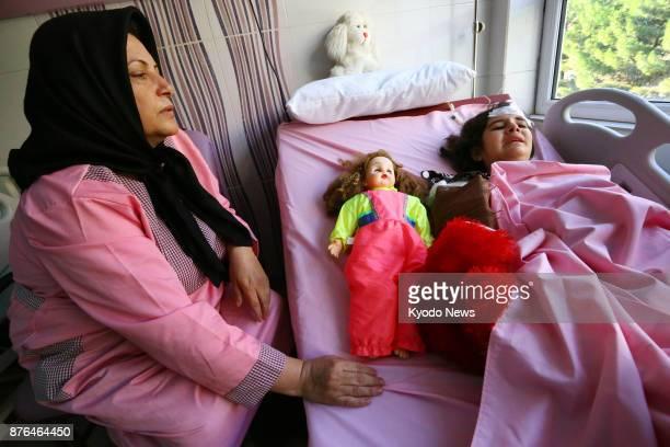 Aliyeh Mohammadi sits beside her 10yearold child Haniyeh Esmaili at a hospital in Kermanshah western Iran on Nov 16 2017 The child was thrown out...