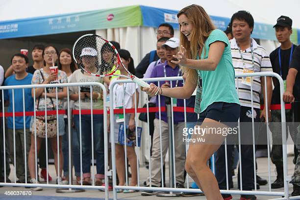 Alize Cornet of France attends a mini tennis games with fans during day four of the 2014 Dongfeng Motor Wuhan Open at Wuhan Optics Valley...