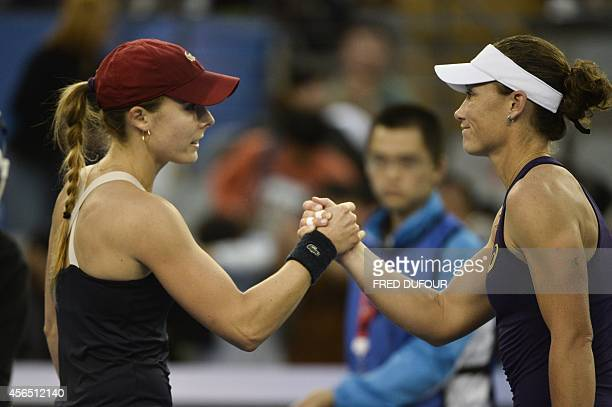 Alize Cornet of France congratulates Samantha Stosur of Australia at the end of their women's singles third round match at the China Open tennis...