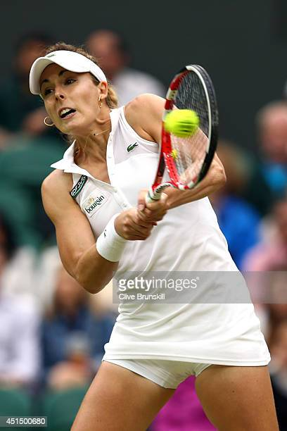 Alize Cornet of France hits a backhand return during her Ladies' Singles fourth round match against Eugenie Bouchard of Canada on day seven of the...