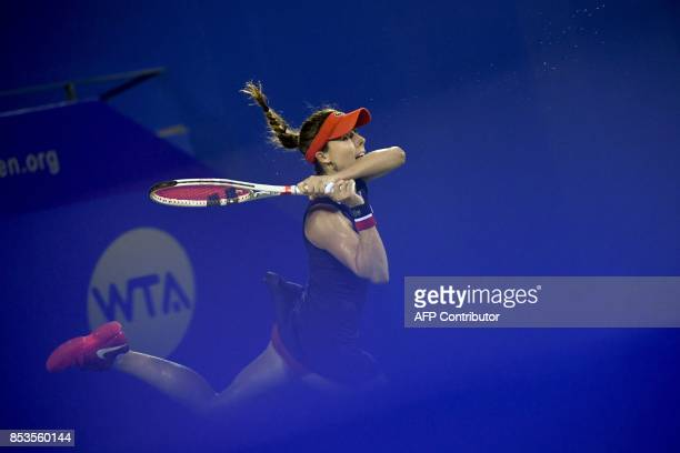Alize Cornet of France hits a return against Anastasia Pavlyuchenkova of Russia during their first round women's match at the WTA Wuhan Open tennis...
