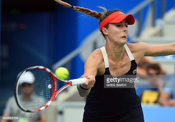 Alize Cornet of France hits a return during her women's singles match against Serena Williams of the US at the Wuhan Open tennis tournament in Wuhan...