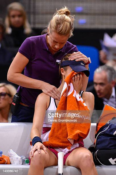 Alize Cornet of France is treated after being injured in her match against Maria Sharapova of Russia during day three of the WTA Porsche Tennis Grand...
