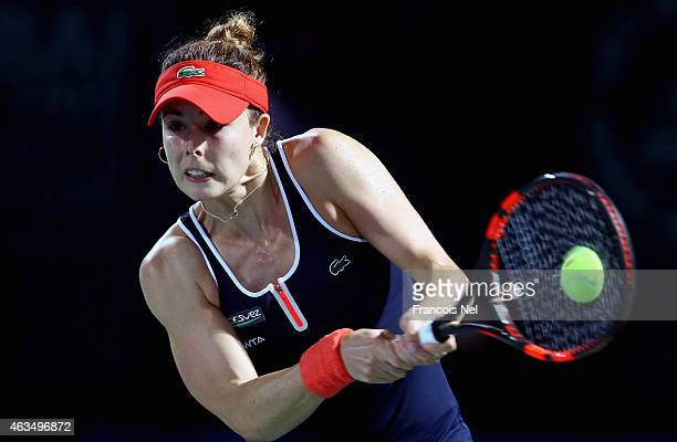 Alize Cornet of France plays a backhand in her match against Kirsten Flipkens of Belguim during day one of the WTA Dubai Duty Free Tennis...