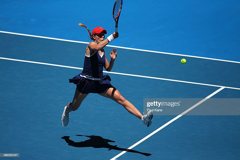 Alize Cornet of France plays a forehand to Anabel Medina Garrigues of Spain in the women's singles match during day seven of the Hopman Cup at Perth Arena on January 3, 2014 in Perth, Australia.