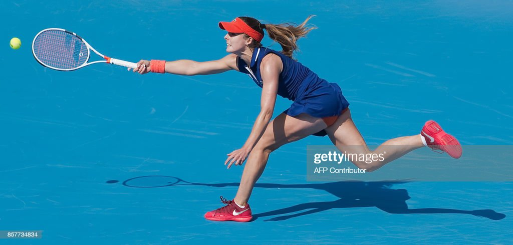 Alize Cornet of France reaches for the ball during her women's singles match against Caroline Garcia of France at the China Open tennis tournament in Beijing on October 5, 2017. /