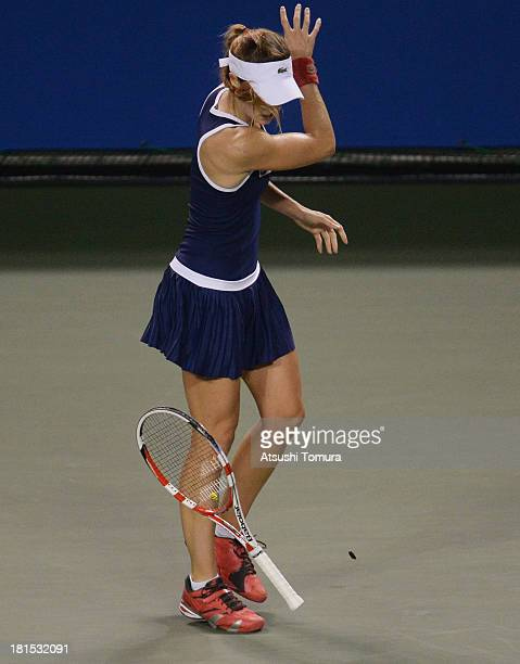 Alize Cornet of France reacts during her women's singles first round match against Samantha Stosur of Australia during day one of the Toray Pan...