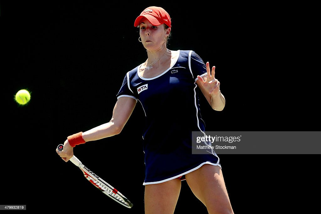 Alize Cornet of France returns a shot to Andrea Petkovic of Germany during the Sony Open at the Crandon Park Tennis Center on March 21, 2014 in Key Biscayne, Florida.