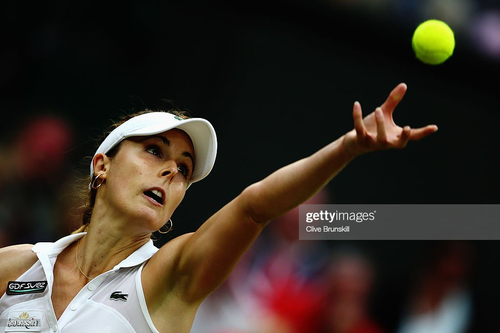 Alize Cornet of France serves during her Ladies' Singles fourth round match against Eugenie Bouchard of Canada on day seven of the Wimbledon Lawn Tennis Championships at the All England Lawn Tennis and Croquet Club on June 30, 2014 in London, England.