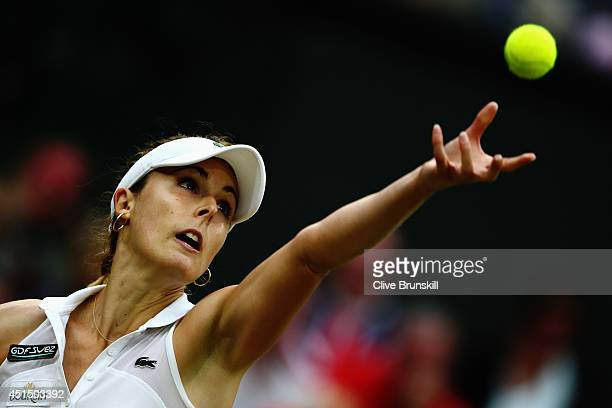 Alize Cornet of France serves during her Ladies' Singles fourth round match against Eugenie Bouchard of Canada on day seven of the Wimbledon Lawn...
