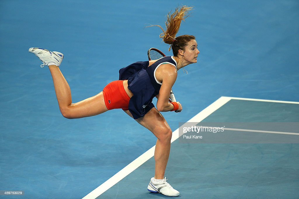 Alize Cornet of France serves to Petra Kvitova of the Czech Republic in the women's singles match during day three of the Hopman Cup at Perth Arena on December 30, 2013 in Perth, Australia.