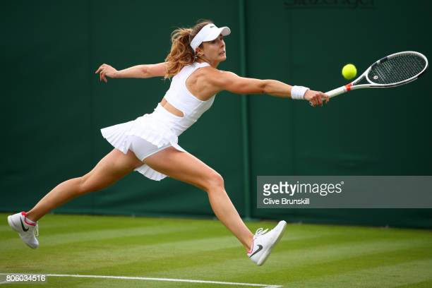 Alize Cornet of France stretches to play a backhand during the Ladies Singles first round match against Camila Giorgi of Italy on day one of the...
