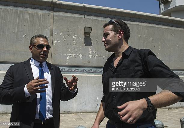 AlJazeera journalists Canadian Mohamed Fahmy and Egyptian Baher Mohamed wait outside Cairo's Torah prison where their trial was due to take place on...