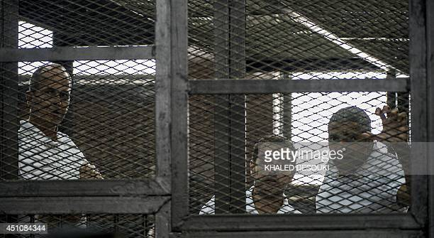 AlJazeera news channel's Australian journalist Peter Greste and his colleagues EgyptianCanadian Mohamed Fadel Fahmy and Egyptian Baher Mohamed listen...