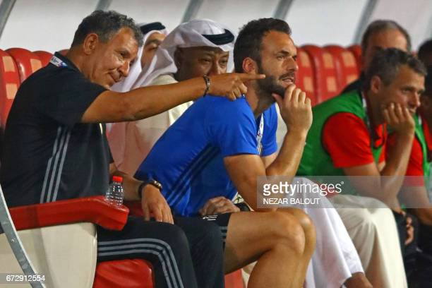 AlJazira's Dutch coach Henk ten Cate speaks with his staff during their AFC Champions League group B football match between Qatar's Lekhwiya and...