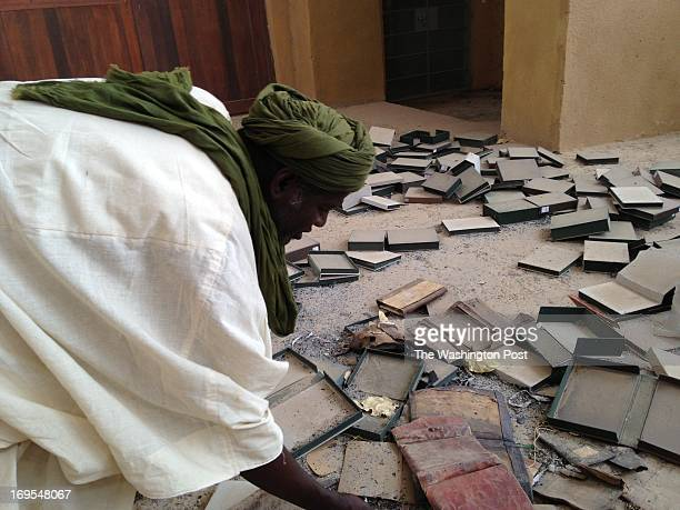 Alkamiss Cisse searches inside the Ahmed Baba Institute amongst empited boxes and burned manuscripts on April 27 2013 in Timbuktu Mali Cisse is an...