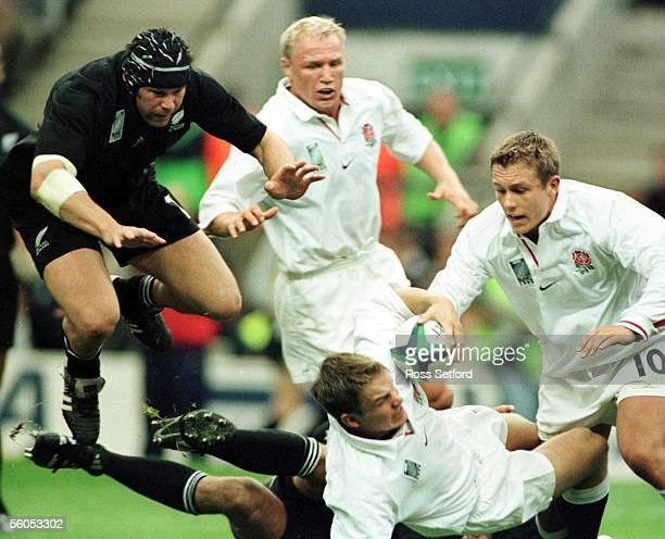 All Black Josh Kronfeld hurdles in on England's Matt Perry in the Rugby World Cup pool match at Twickenham Saturday The All Blacks won 3016